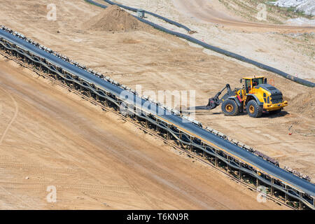 Brown coal open pit landscape with conveyor belt and dozer