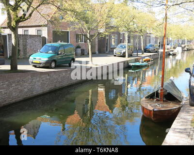 View of one of the canals that runs through the pretty town of Enhuizen, a popular tourist destination in North Holland; April 2019 - Stock Photo