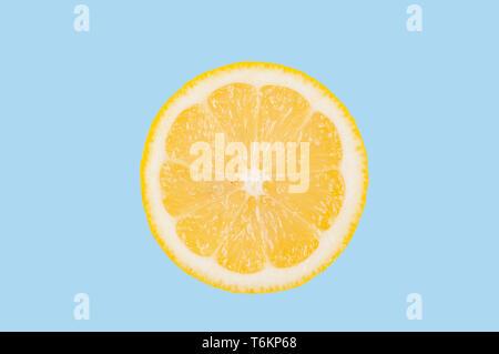 Fresh lemon slice on pastel blue background - Stock Photo