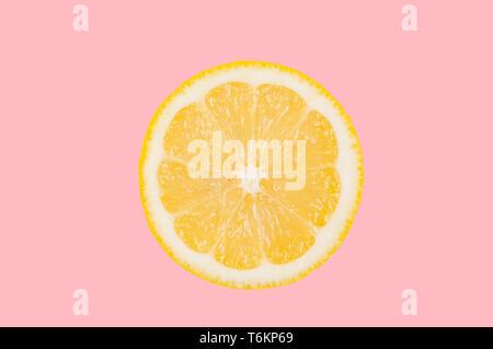 Fresh lemon slice on pastel pink background - Stock Photo