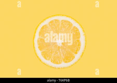 Fresh lemon slice on pastel yellow background - Stock Photo