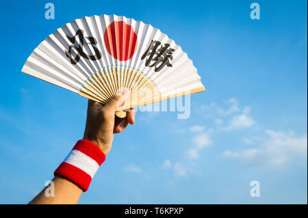 Hand of sports supporter with Japan flag colors wristband holding fan decorated with kanji characters spelling out hisshō, certain victory in English - Stock Photo