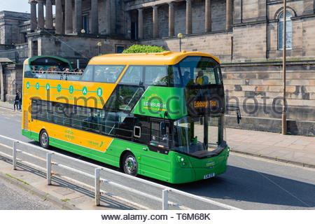 Sightseeing bus near Royal Mile with historic buildings in Edinburgh - Stock Photo
