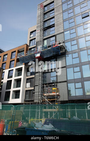April 2019 - Mast climber at work on the external elevation of a new office at the Finzals Reach development in Bristol. - Stock Photo