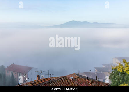 Chiusi Scalo mist fog sunrise of rooftop houses buildings in Italy near Tuscany with soft clouds covering blanketing town in summer - Stock Photo