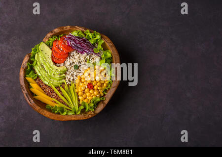 Wooden bowl with chickpea, avocado, wild rice, quinoa, tomatoes, greens, cabbage, lettuce on stone background. Vegetarian superfood. Top view with cop - Stock Photo