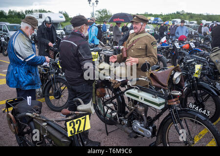 A man dressed in First World War uniform by his classic period Triumph motorcycle at the Banbury Run. - Stock Photo