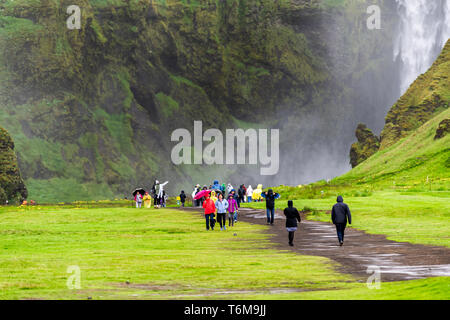 Skogafoss, Iceland - June 14, 2018: Waterfall on cliff with green grass meadow and many tourists people walking with ponchos on trail road in rainy mo - Stock Photo