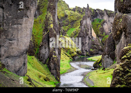 Landscape high angle view of canyon in Fjadrargljufur, Iceland with large cliffs and river green moss grass - Stock Photo