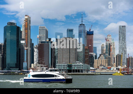 April 27, 2019 - New York City, USA:  New York City water taxi on the East River, with the skyline of Lower Manhattan in the background. - Stock Photo