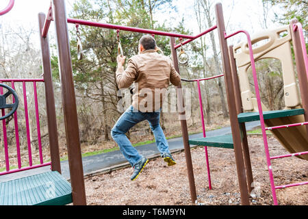 Young fit man exercising doing chin pull ups on bar in playground park in autumn winter or spring calisthenics - Stock Photo