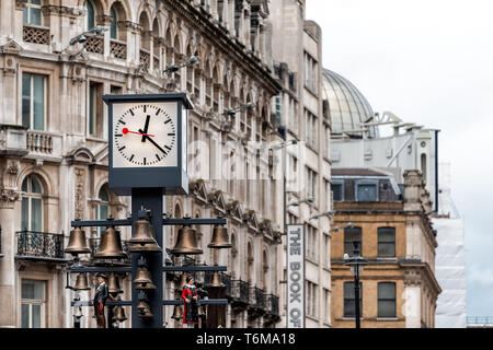 London, UK - September 12, 2018: Leicester Square clock face during day in city with old architecture and the book of mormon sign - Stock Photo
