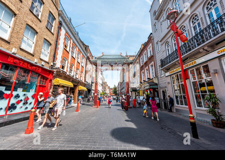 London, UK - June 24, 2018: Wide angle view of Chinatown China town Wardour street road with many people in downtown city with Chinese red gate - Stock Photo