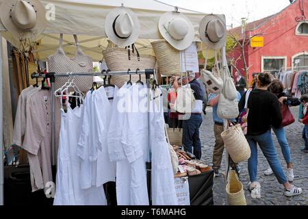 LX Factory street market selling white cotton garments, straw hats, linen clothing and shoulder bags Alcantara Lisbon Lisboa Portugal  KATHY DEWITT - Stock Photo