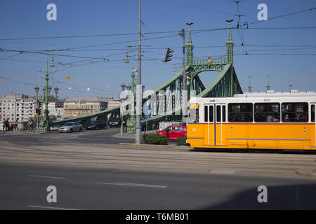 Yellow tram passing by in front of Liberty Bridge in Budapest, Hungary. - Stock Photo