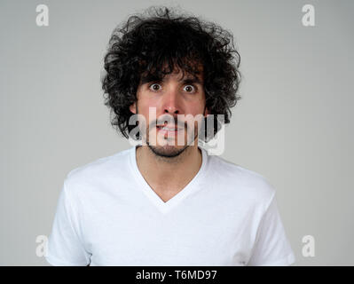 Annoyed young millennial man with an angry face looking mad and furious feeling frustrated. Close up studio shot Isolated on white background. People, - Stock Photo