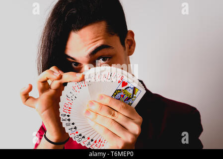 magician doing tricks with a deck of cards. - Stock Photo