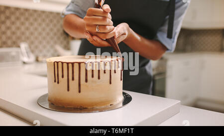 Close up of hands of a female chef with confectionery bag squeezing liquid chocolate on cake. Pastry chef decorating a cake in kitchen. - Stock Photo