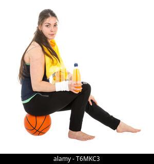 Pretty woman in sports wear sitting on basketball drinking juice - Stock Photo