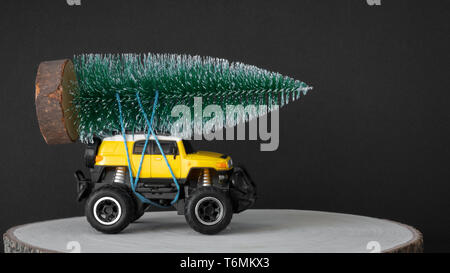 christmas tree on a yellow toy car - Stock Photo