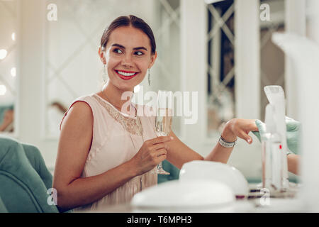 Appealing woman with tied hair being in great mood while drinking sparkling wine - Stock Photo