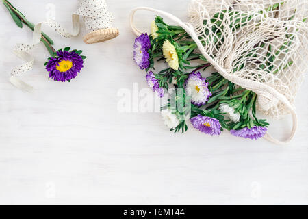 Bouquet of colorful asters in a mesh bag and decorative ribbon, on white wooden background. - Stock Photo