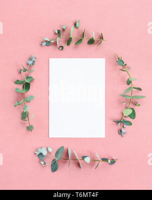 Blank paper sheet with copy space framed by eucalyptus branches, on pastel pink canvas. - Stock Photo