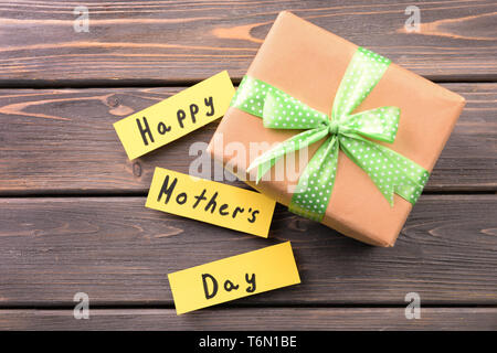 Gift box for Mother's Day on wooden background - Stock Photo