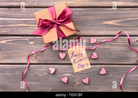 Gift box for Mother's Day with greeting card on wooden background - Stock Photo