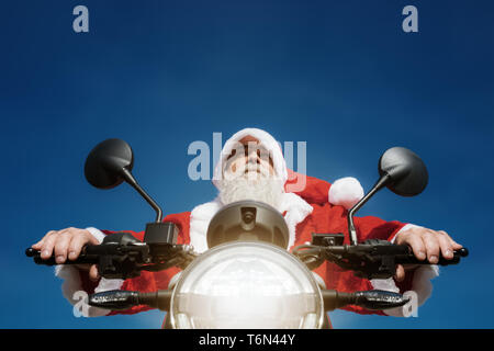 man on a motorbike in a typical Santa Claus costume - Stock Photo
