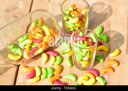 a glass jar full of colored candies on wood background - Stock Photo