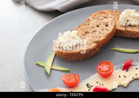 Toasted bread served with cream cheese and butter on plate, closeup - Stock Photo