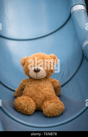 Cute teddy bear on playground slide - Stock Photo