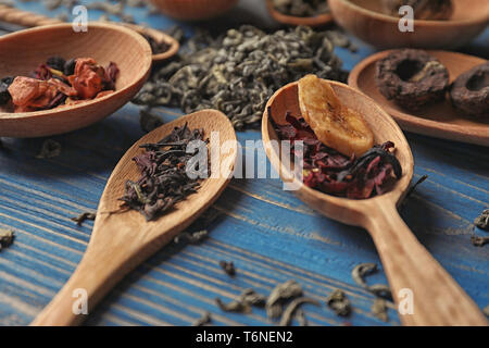 Spoons with different types of dry tea leaves on wooden background - Stock Photo