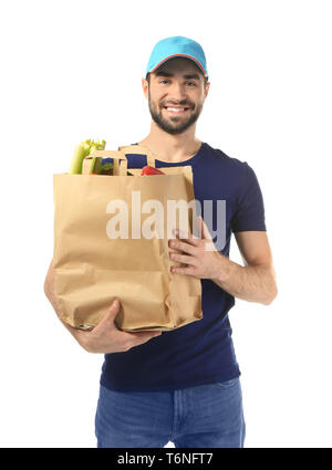 Delivery man holding paper bag with food on white background - Stock Photo