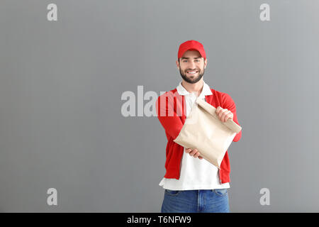 Delivery man holding paper bag with food on grey background - Stock Photo