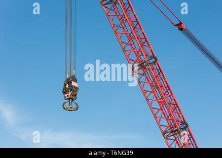 Red crane boom with hook against blu sky - Stock Photo