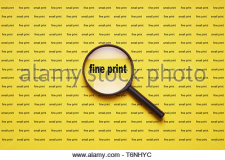 fine print enlarged with magnifying glass magnifier loupe - Stock Photo