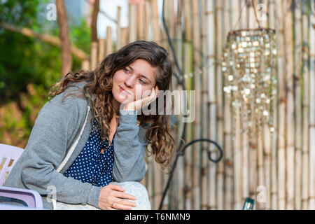 Young woman face looking away happy smiling in zen bamboo garden with shiny decorations wind chimes sitting on chair - Stock Photo