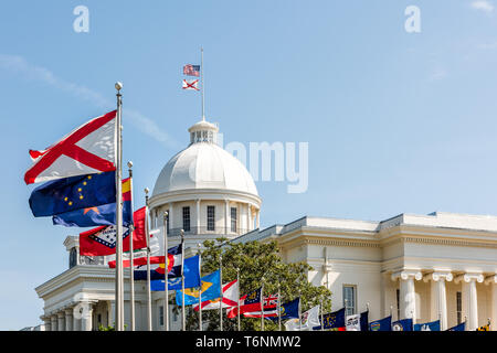 Montgomery, USA State capitol building in Alabama during sunny day with old historic architecture of government and many row of flags by dome - Stock Photo