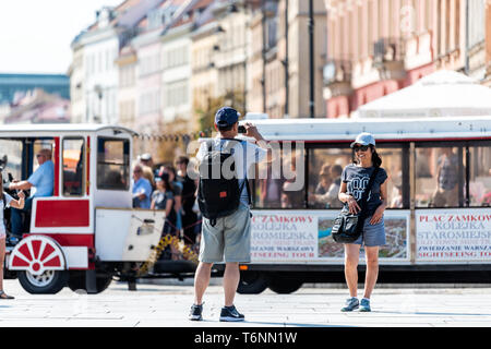 Warsaw, Poland - August 23, 2018: Old town historic road during sunny summer day with trolley tour tram bus and people taking picture - Stock Photo