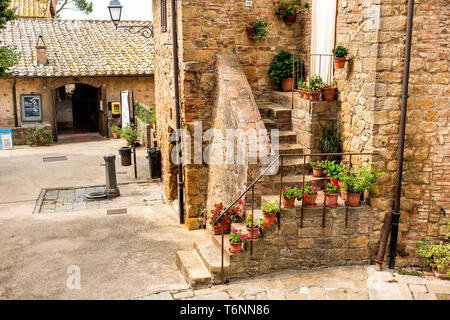 Monticchiello, Italy - August 26, 2018: Val D'Orcia countryside in Tuscany with empty street in small town village with nobody and plants on typical s - Stock Photo