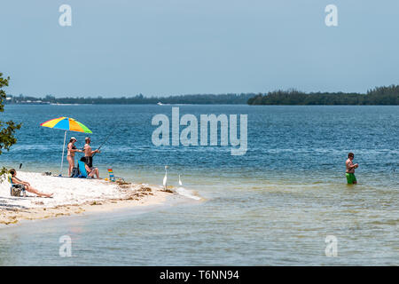 Sanibel Island, USA - April 29, 2018: Causeway beach with people on coast during sunny day fishing - Stock Photo