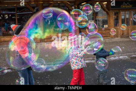 Children catching giant soap bubbles - Stock Photo