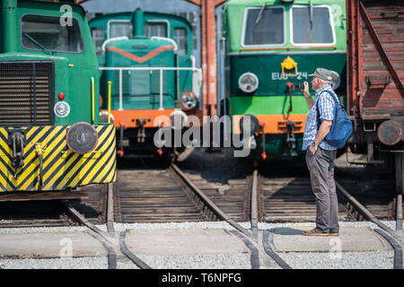 Tourist looking at the old locomotives - Stock Photo