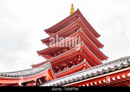 Tokyo, Japan Asakusa with low angle pagoda roof view of Sensoji temple shrine with red architecture on cloudy day
