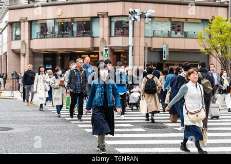 Tokyo, Japan - March 31, 2018: Ginza district with many people Japanese walking crossing street with woman in mask - Stock Photo