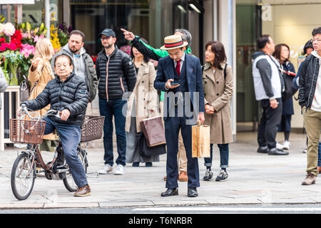 Tokyo, Japan - March 31, 2019: Ginza district with many people Japanese locals waiting crossing street with man in vintage costume - Stock Photo