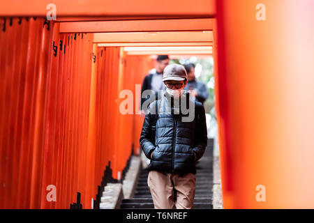 Tokyo, Japan - March 31, 2019: Hie shrine gate entrance stairs steps path with man in mask walking down up in Akasaka district area - Stock Photo