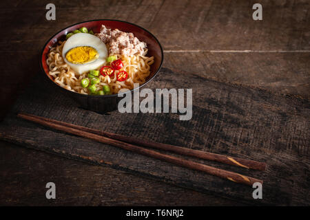 Instant noodle with pork, egg and vegetables on black bowl on the wood table there is chopstick placed in front of. - Stock Photo